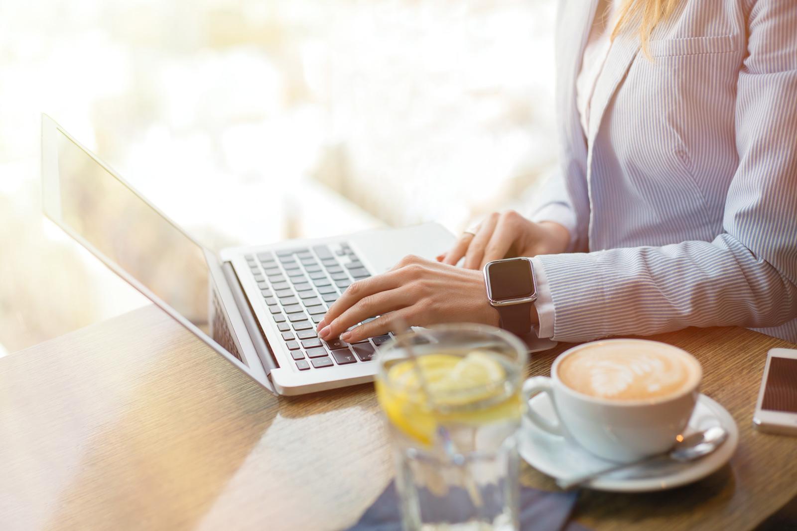 Frau arbeitet im Restaurant am Laptop