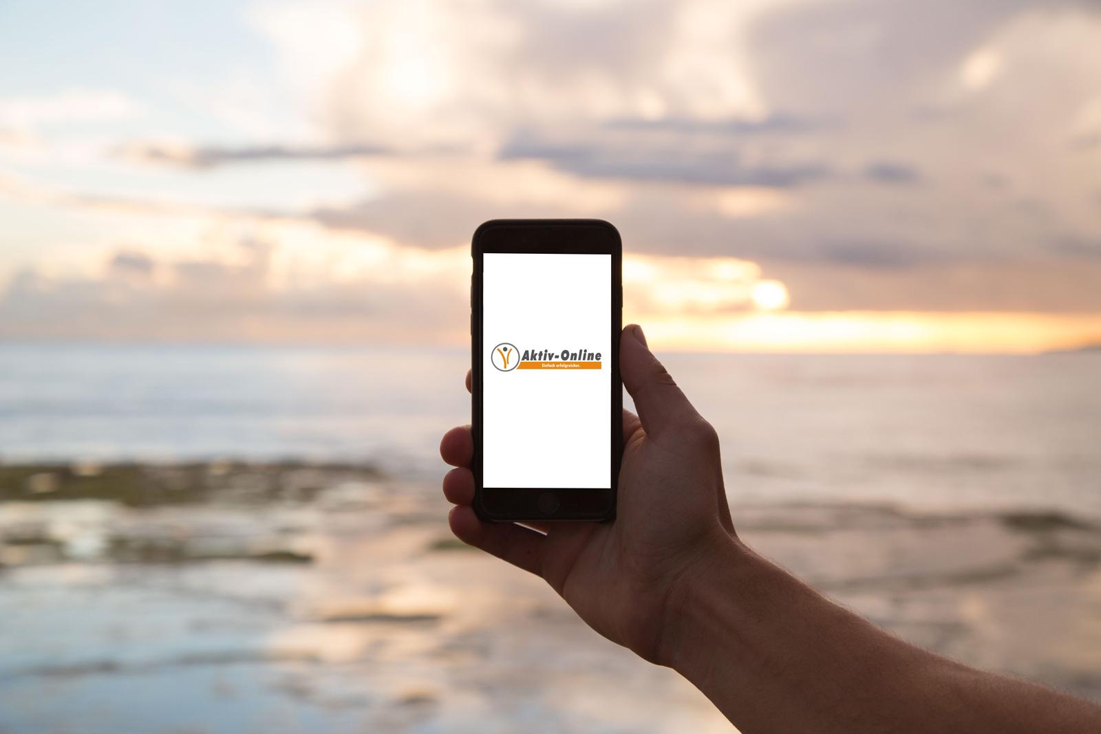 Smartphone Hand Sonnenuntergang am Meer